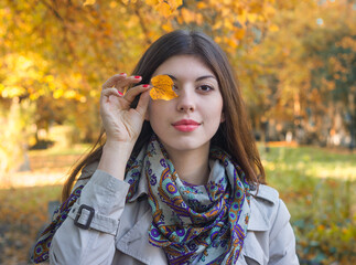 Portrait of a happy young woman with an autumn leaf at the eye.