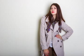 A beautiful fashionable woman in a light raincoat and a neckerchief poses on a light background.