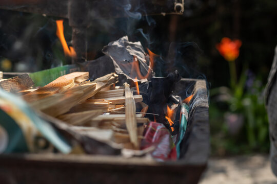 Making fire in a rustic barbecue grill with wood and charcoal, lot of flame and smoke