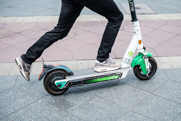 Closeup of a person using a Lime E-scooter or Electric scooter