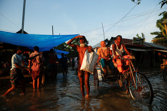 A man blocks sunlight for a clear vision as he walks on a flooded road in Jamalpur