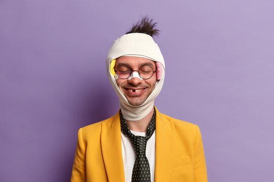 Portrait of funny smiling man has missing teeth after serious trauma, stands with closed eyes, bruised skin, bandaged head, fell during bike riding, has recovery period, isolated on purple wall
