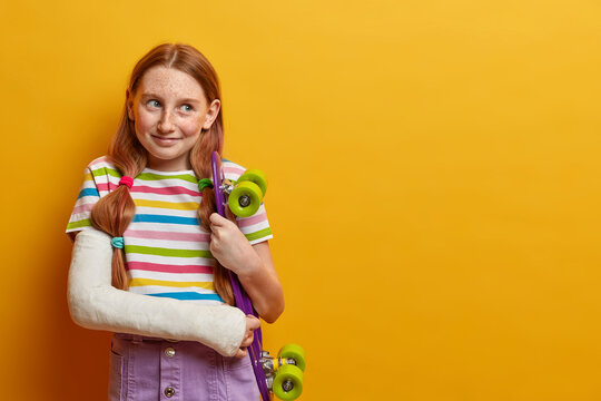 Beautiful girl has broken arm after falling from skateboard, enjoys extreme sport, wears cast, injured after accident during summer time, hopes for fast recovery and riding again, isolated on yellow