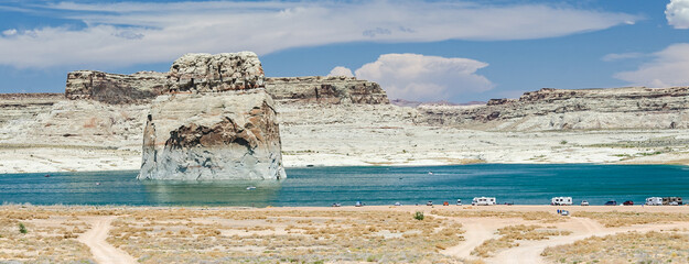 Scenic view of Lone Rock Beach with camping vehicles at Lake Powell in the desert in the United States