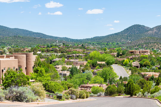 Cityscape view in Santa Fe, New Mexico mountains of road street through community neighborhood with green plants summer and adobe traditional houses