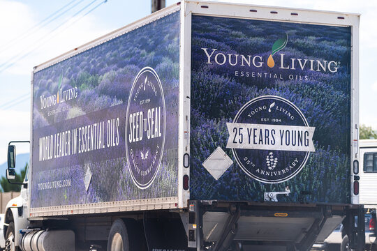 American Fork, USA - July 29, 2019: Young Living Essential Oils company delivery truck sign near warehouse on highway road in Utah cars in traffic