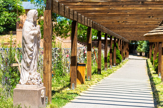 Chimayo, USA - June 19, 2019: El Santuario de Chimayo sanctuary church in the United States with entrance passage and virgin Mary statue