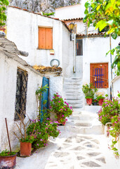 Fototapete - Old narrow street with flowers in Anafiotika, Plaka district, Athens, Greece. Plaka is tourist attraction of Athens.
