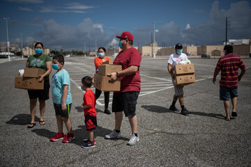 Residents affected by economic fallout from the pandemic hold groceries provided by the Houston Food Bank in Texas
