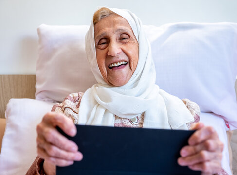 Portrait of senior Arabic woman using electronic tablet at home