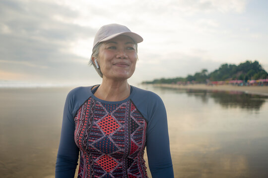 portrait of fit and happy middle aged woman after beach running workout - 40s or 50s attractive mature lady with grey hair smiling cheerful after jogging enjoying fitness healthy lifestyle