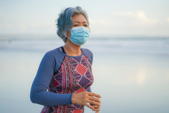 new normal running workout with face mask - attractive and happy middle aged woman on her 40s or 50s doing post quarantine jogging at beautiful beach in healthy lifestyle