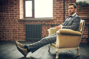 groom relaxed in an armchair