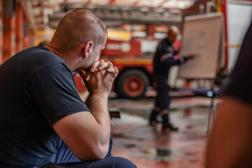Closeup of firefighter sitting and listening boss who is talking about tactic how they gonna extinguish the fire. Fire brigade interior.
