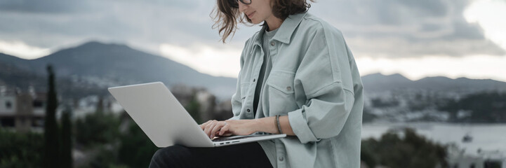 Beautiful curly young girl with glasses working on a laptop with a city view. Modern technologies and urban lifestyle