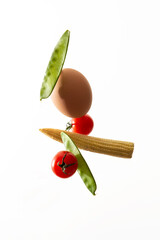 composition of flying vegetables and ingredients beans tomatoes an egg and corn on white background