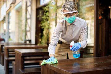 Young waitress disinfecting tables at outdoor cafe during coronavirus epidemic.