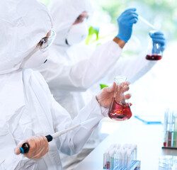 Scientists in protection suits and masks working in research lab using laboratory equipment: microscopes, test tubes.