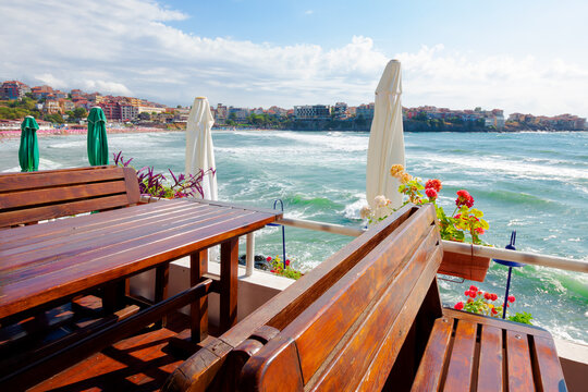 empty terrace of a restaurant on the sea. beautiful view in to the bay in morning light. decorative umbrella above wooden tables and seats. sunny weather
