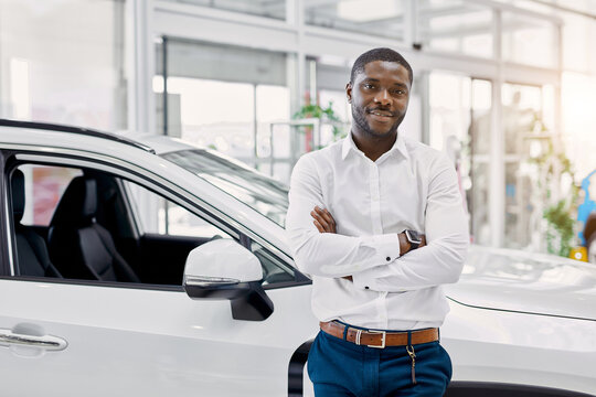 portrait of smiling afro man in white shirt, he stands next to new car, look at camera.