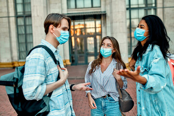 A group of students wearing protective medical masks talk outside the campus.