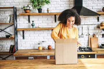 A young multi-racial girl received an online delivery order. Attractive woman with Afro hairstyle unpack the box in the kitchen