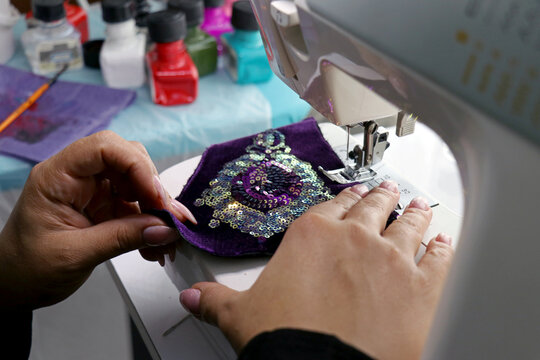 Nasibeh Tehrani designs and sews patterned masks for sale at her home in Tehran