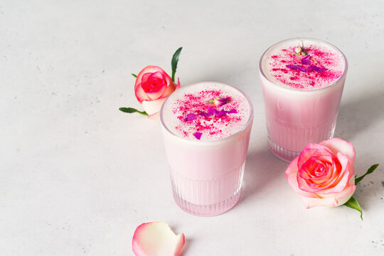 Ice rose latte in glass with pink flowers and petal on white or grey background