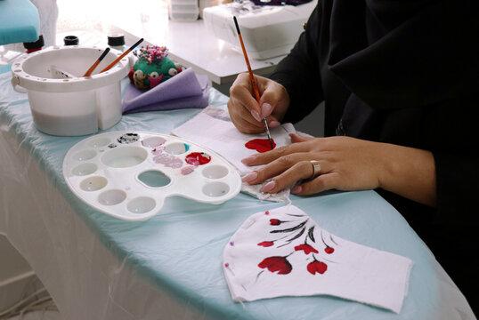 Nasibeh Tehrani colors her patterned masks for sale at her home in Tehran