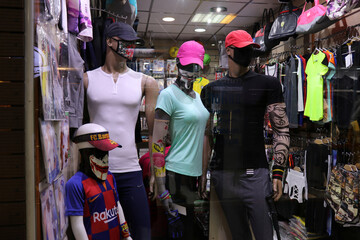 Mannequins with patterned masks are displayed in a shop window in Tehran