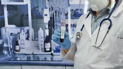 Doctor holding a tube of covid-19 test in a laboratory.