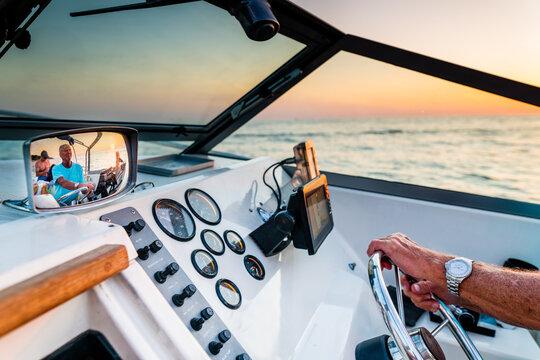 Senior man driving a boat at sunset