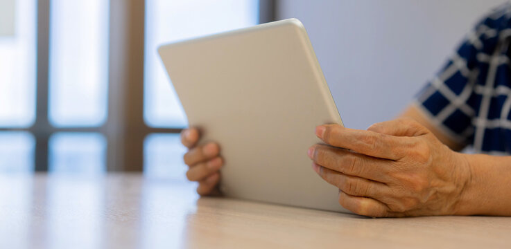 close up senior woman hand holding tablet to watching multimedia from website or video call with family in living room for mature person with lifestyle and technology