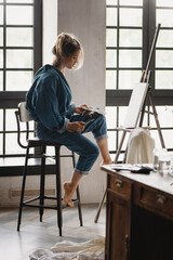 Beautiful female artist painting picture in studio.