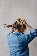 Woman making hairstyle with painting brushes.