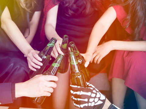 Cropped image of 5 teenagers toasting beer bottles to celebrate Halloween at the party. Halloween concept.