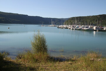 Sail boats harbor on a turquoise lake
