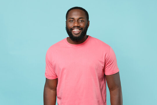 Smiling young african american man guy in casual pink t-shirt posing isolated on pastel blue background studio portrait. People sincere emotions lifestyle concept. Mock up copy space. Looking camera.