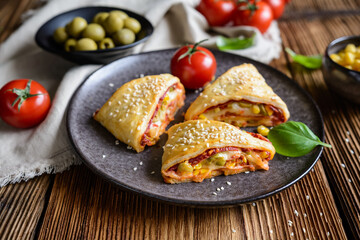 Puff pastry pizza triangle rolls stuffed with tomato sauce, ham, cheese, corn, olives and sprinkled with sesame seeds