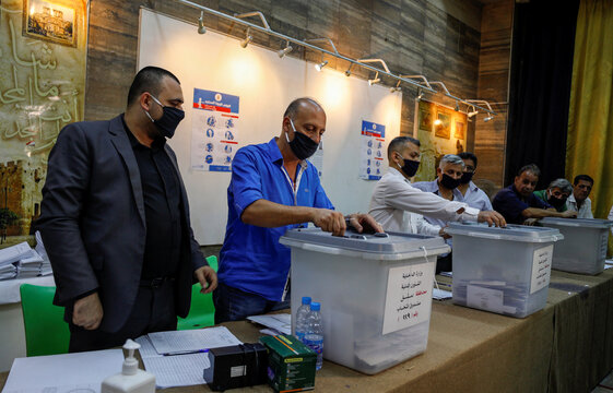 Men prepare to open ballot boxes at a polling station to start the counting process during parliamentary election in Damascus