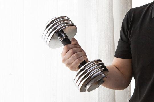 ダンベルを使って自宅の部屋で筋トレする男性
