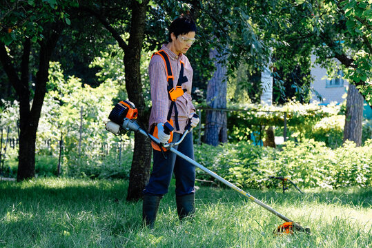 Woman mowing the grass in garden. Lawn care concept