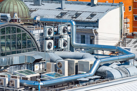 Ventilation system on roof of the building. Air conditioners near ventilation pipes. Engineering communications on roof of a high-rise building. Concept - cleaning air in the building.