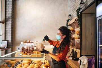 Beautiful young female worker with protective mask on face working in bakery.