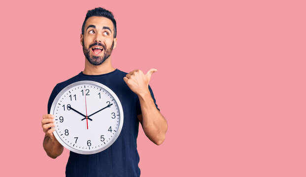 Young hispanic man holding big clock pointing thumb up to the side smiling happy with open mouth