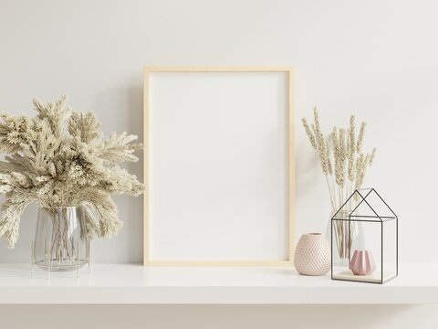 Wooden frame leaning on white shelf in bright interior with plants on the table with plants in pots on empty wall background.