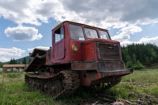 an old logging truck, rusty and abandoned in a field against the backdrop of a beautiful forest, as a symbol of the collapse of industry in Russia and Siberia. mismanagement