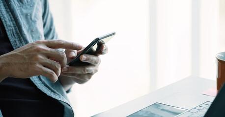 Close up man using smart phone at home