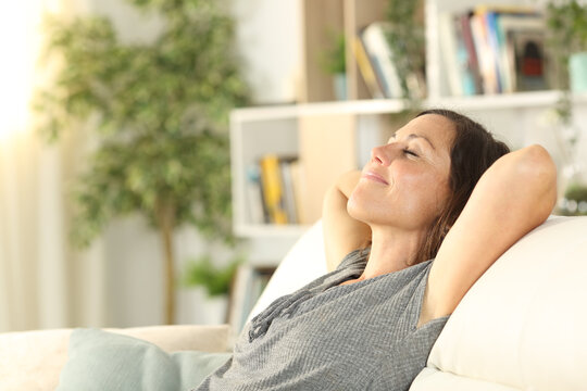 Happy adult woman relaxing in the sofa at home
