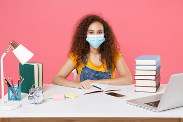 African american student girl in sterile face mask employee in office sit work at desk isolated on pink background. Business career covid Education in school university college concept. Looking camera